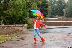Giovane donna felice con l'ombrello luminoso sotto pioggia fotografia stock