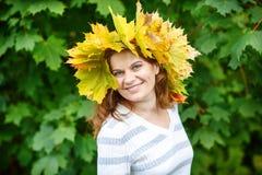 Giovane donna felice con la ghirlanda delle foglie di acero di autunno in parco. Fotografie Stock