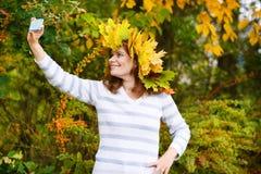 Giovane donna felice con la ghirlanda delle foglie di acero di autunno in parco. Fotografia Stock