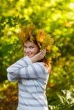 Giovane donna felice con la ghirlanda delle foglie di acero di autunno in parco. Immagini Stock Libere da Diritti