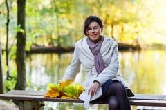 Giovane donna felice con la ghirlanda delle foglie di acero di autunno in parco. Immagini Stock