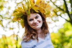 Giovane donna felice con la ghirlanda delle foglie di acero di autunno in parco. Immagine Stock