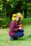 Giovane donna felice con la ghirlanda delle foglie di acero di autunno in parco Fotografie Stock