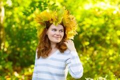 Giovane donna felice con la ghirlanda delle foglie di acero di autunno in parco Fotografia Stock