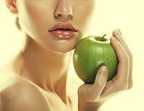 Giovane donna felice con la mela verde - isolata su bianco immagini stock