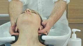 Giovane donna felice con la testa di lavaggio del parrucchiere al salone di capelli immagini stock