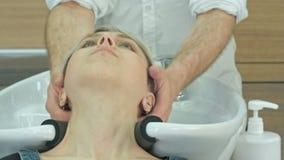 Giovane donna felice con la testa di lavaggio del parrucchiere al salone di capelli video d archivio