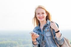 Giovane donna felice con lo smartphone a disposizione con il sorriso che esamina macchina fotografica Viaggio, Internet, tecnolog immagini stock libere da diritti