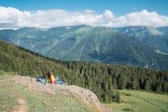 Giovane donna felice con lo zaino che sta su una roccia che guarda ad una valle qui sotto immagine stock
