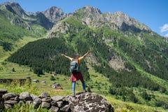 Giovane donna felice con lo zaino che sta su una roccia con le mani sollevate e che guarda ad una valle qui sotto immagini stock