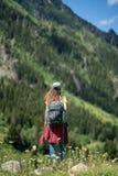 Giovane donna felice con lo zaino che sta su una roccia con le mani sollevate e che guarda ad una valle qui sotto fotografia stock