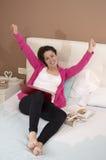 Giovane donna felice con un computer portatile e armi su in camera da letto Immagini Stock