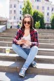 Giovane donna felice con una tazza fresca che si siede sulle scale e che per mezzo del suo smartphone Fotografie Stock Libere da Diritti