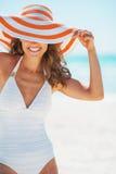 Giovane donna felice in costume da bagno che si nasconde dietro il cappello della spiaggia Fotografie Stock