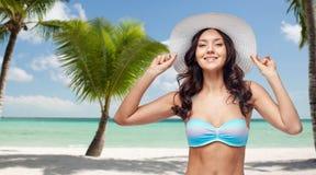Giovane donna felice in costume da bagno del bikini e cappello del sole fotografia stock