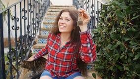 Giovane donna felice davanti alla nuova casa con le chiavi stock footage