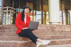 Giovane donna felice dei pantaloni a vita bassa che lavora ai outdors del computer portatile Ragazza dello studente che utilizza  Immagine Stock Libera da Diritti