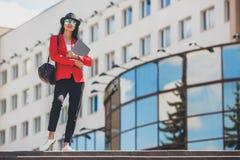 Giovane donna felice dei pantaloni a vita bassa che lavora ai outdors del computer portatile Ragazza dello studente che utilizza  Fotografia Stock
