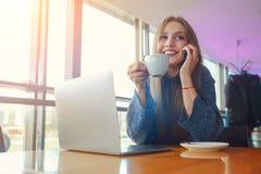 Giovane donna felice dei pantaloni a vita bassa con la tazza di cofe che parla sul telefono dentro al caffè Computer portatile su Fotografie Stock Libere da Diritti