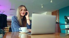 Giovane donna felice dei pantaloni a vita bassa con la tazza di cofe che parla sul telefono dentro al caffè Computer portatile su stock footage