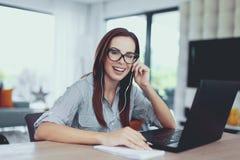 Giovane donna felice del nerd che impara agli esami all'interno fotografia stock