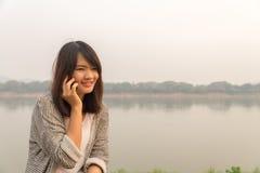 Giovane donna felice del ritratto che sorride e che cammina nella via facendo uso della conversazione sullo smartphone e dell'esa Immagine Stock