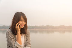Giovane donna felice del ritratto che sorride e che cammina nella via facendo uso della conversazione sullo smartphone e dell'esa Fotografia Stock Libera da Diritti