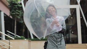 Giovane donna felice di affari che balla con l'ombrello che controlla se la fermata della pioggia Lei che sorride e che gode dell archivi video