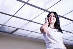 Giovane donna felice di affari che comunica dal cellulare Fotografie Stock