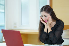 Giovane donna felice di affari che esamina lo schermo del computer portatile sorpreso Fotografia Stock