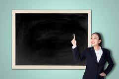 Giovane donna felice di affari che indica la lavagna vuota Immagini Stock Libere da Diritti