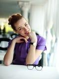 Giovane donna felice di affari che si siede alla tavola Fotografia Stock Libera da Diritti
