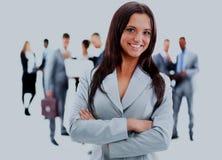 Giovane donna felice di affari che sta davanti al suo gruppo Fotografie Stock