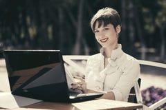 Giovane donna felice di affari con il computer portatile al caffè del marciapiede Immagine Stock