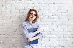 Giovane donna felice di affari con una cartella all'edificio per uffici Immagine Stock