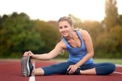 Giovane donna felice di misura che fa allungando gli esercizi Fotografia Stock