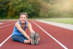Giovane donna felice di misura che fa allungando gli esercizi Immagini Stock