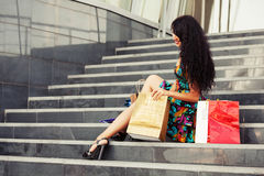 Giovane donna felice di modo con i sacchetti della spesa che si siedono sui punti Fotografie Stock Libere da Diritti
