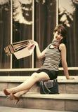 Giovane donna felice di modo con i sacchetti della spesa sui punti Fotografia Stock