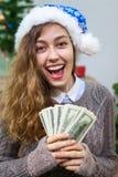 Giovane donna felice e di risata con denaro contante a disposizione come presente alla notte di Natale Fotografia Stock