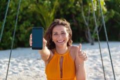 Giovane donna felice messa su un'oscillazione che mostra uno schermo verticale del telefono Sabbia e giungla bianche come fondo fotografia stock
