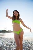 Giovane donna felice nel dancing verde del bikini alla spiaggia Immagini Stock Libere da Diritti