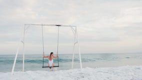 Giovane donna felice nella guida bianca del costume da bagno sull'oscillazione che gode della vista del mare Concetto di vacanza video d archivio