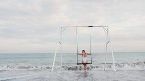 Giovane donna felice nella guida bianca del costume da bagno sull'oscillazione che gode della vista del mare Concetto di vacanza archivi video