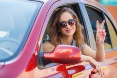 Giovane donna felice nella guida di veicoli sulla strada Immagine Stock
