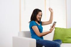 Giovane donna felice per mezzo di un PC del ridurre in pani Immagine Stock Libera da Diritti