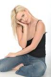 Giovane donna felice premurosa sveglia che si siede sul rilassamento del pavimento Fotografia Stock