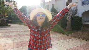 Giovane donna felice sorridente nell'iarda della sua residenza stock footage