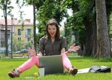 Giovane donna felice su un computer portatile Immagini Stock
