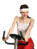 Giovane donna felice su una bicicletta di addestramento Immagine Stock
